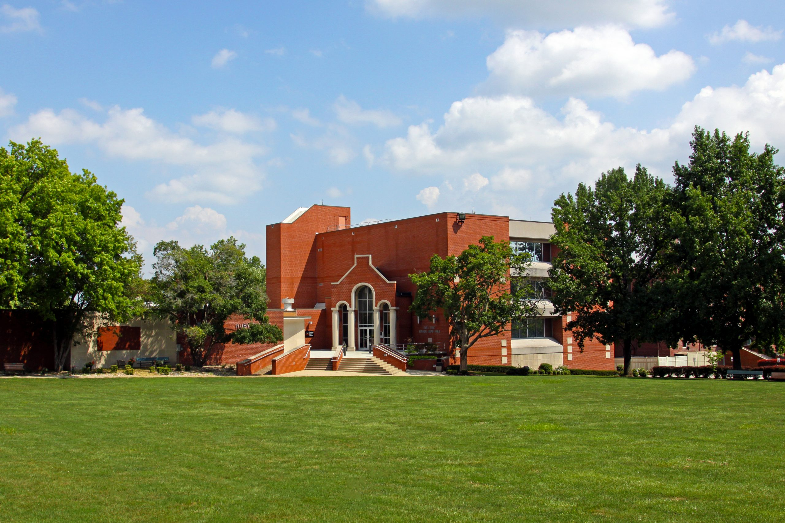 A collegiate brick building sits amid a bright green lawn on a sunny day with fluffy white clouds.